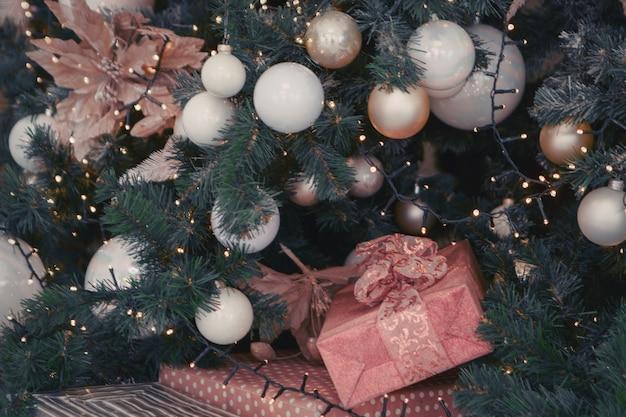 Vacances, nouvel an, décoration et concept de célébration - gros plan sur un arbre de noël décoré de boules et de jouets