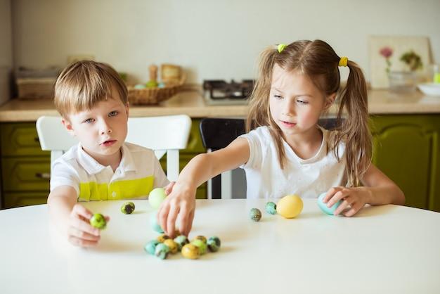 Vacances De Pâques Enfants Gais Mignons Tenant Des Oeufs Décorés à La Maison Photo Premium