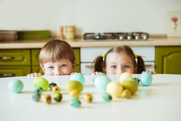 Vacances de pâques enfants gais mignons tenant des oeufs décorés à la maison