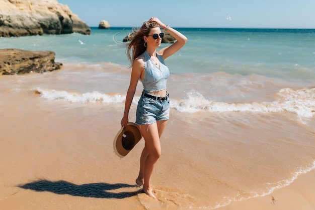 Vacances à la plage. belle femme en chapeau de soleil bénéficiant d'une parfaite journée ensoleillée marchant sur la plage. bonheur et félicité.