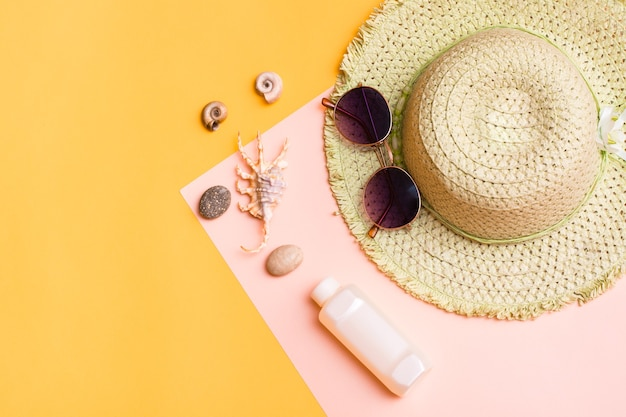 Vacances à la plage. un chapeau de paille, des lunettes de soleil, une bouteille de crème solaire et des coquillages sur un carton jaune-rose. articles pour bronzer et bronzer. vue de dessus