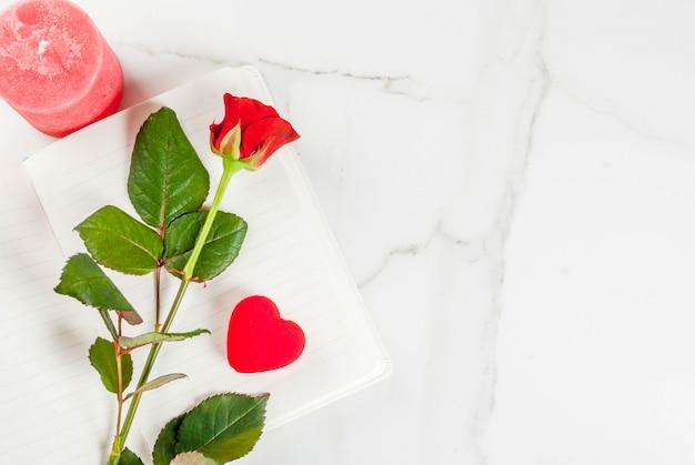Vacances, saint valentin. bouquet de roses rouges, cravate avec un ruban rouge, avec bloc-notes vierge, coffret cadeau enveloppé et bougie rouge. sur une table en marbre blanc, vue de dessus du fond