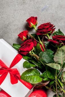 Vacances, saint valentin. bouquet de roses rouges, cravate avec un ruban rouge, avec coffret cadeau enveloppé et bougie rouge. sur une table en pierre grise, vue de dessus du fond