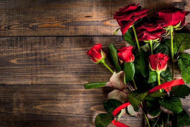 Vacances, saint valentin. bouquet de roses rouges, cravate avec un ruban rouge, avec coffret cadeau enveloppé. sur une table en bois, vue de dessus du fond