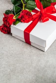 Vacances, saint valentin. bouquet de roses rouges, cravate avec un ruban rouge, avec coffret cadeau enveloppé. sur une table en pierre grise, copyspace