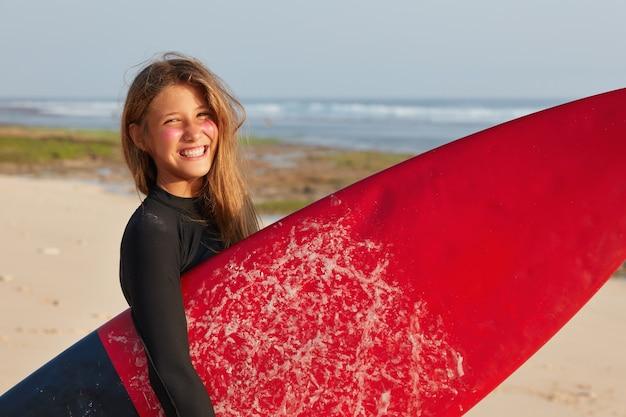 Vacances, style de vie, concept de tourisme. surfeur satisfait en combinaison, porte planche cirée