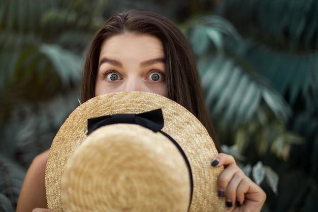 Vacances, tourisme. la fille se cache avec surprise pour son chapeau. les yeux en gros plan, les émotions.
