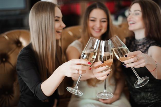 Vacances, vie nocturne, enterrement de vie de jeune fille et concept de personnes - femmes souriantes avec des verres à champagne.