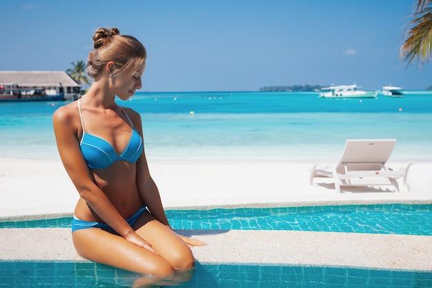 Vacances de voyage - belle jeune jolie fille blonde de retour en bikini sur son corps sexy de sport parfait se détendre dans la piscine près de la plage paradisiaque sur la plage tropicale des caraïbes aux maldives lors d'une journée ensoleillée à l'hôtel