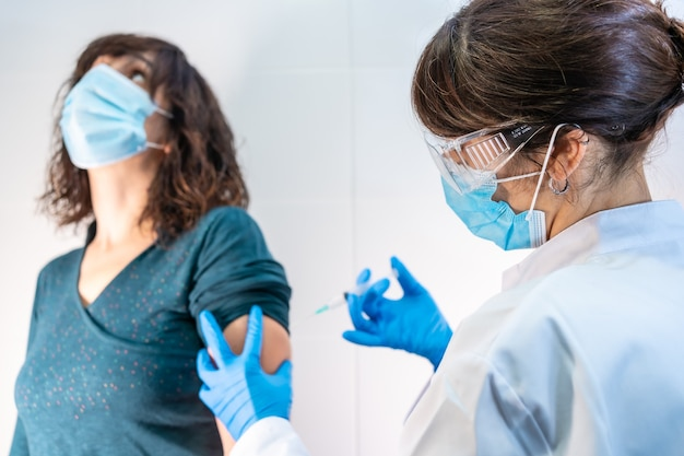 Vaccin contre le coronavirus appliqué à une jeune femme par un médecin. anticorps, immuniser la population.