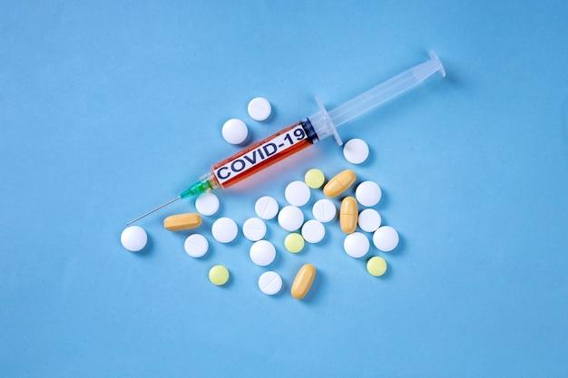 Vaccin contre le coronavirus à la seringue et pilules sur la surface bleue