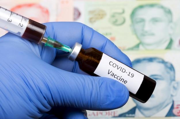 Vaccin contre covid-19 sur le fond du dollar de singapour