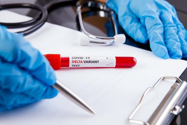 Vaccin covid 19 delta variant et test de sang à la main sur fond blanc. vaccin contre le coronavirus