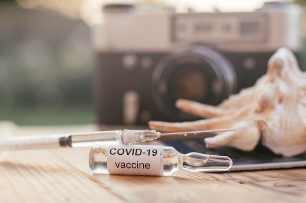 Le vaccin covid-19, la seringue, le coquillage, l'appareil photo rétro et le passeport se trouvent sur une table en bois au soleil. retour au voyage et à la vie normale après le concept de vaccination contre le coronavirus