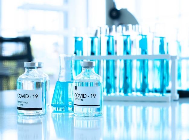 Vaccin covid en bouteille avec tube à essai et microscope en arrière-plan dans la salle des tours d'essai.