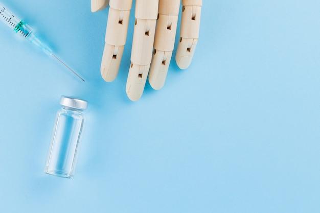 Vaccin, seringue et main humaine en bois. ampoule médicale et seringue sur fond bleu