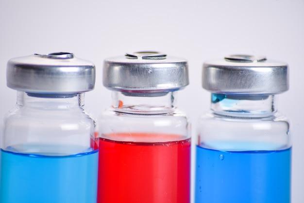 Vaccin, vaccination contre le coronavirus, prévention de la grippe covid-19, concept de vaccination. flacon ou ampoules de médicament trois couleurs rouge et bleu