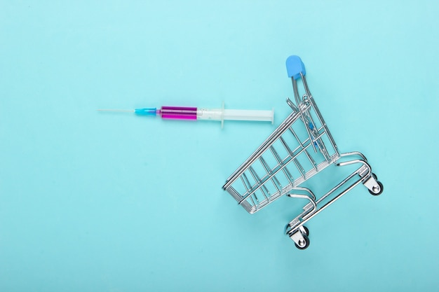Vaccination. chariot de supermarché avec seringue sur fond bleu pastel. vue de dessus