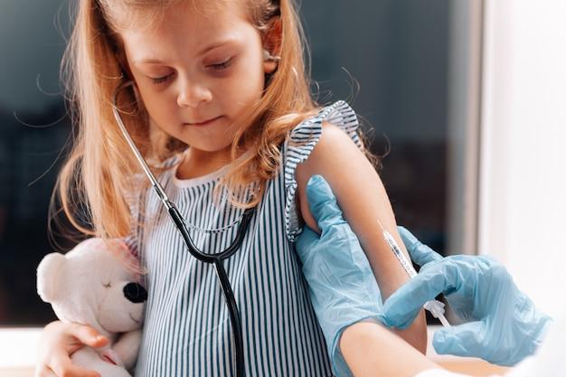 Vaccination des enfants. médecin examinant un enfant dans un hôpital. covid-19
