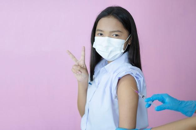 Vaccination des étudiants asiatiques sur fond rose.