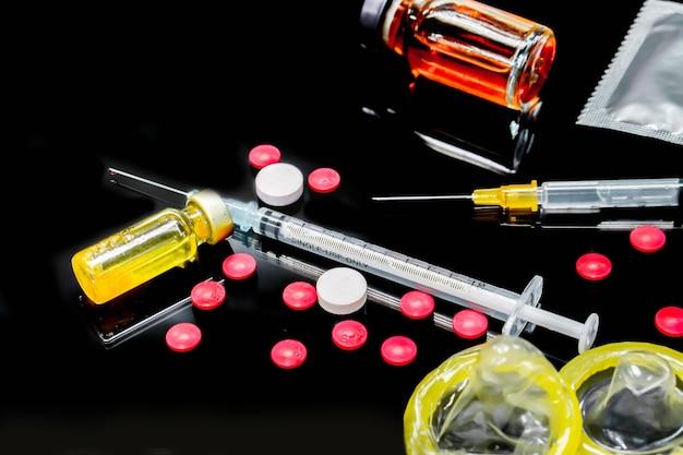 Les vaccins en flacon, les médicaments blancs et rouges avec une seringue en plastique et des préservatifs isolent sur fond noir. échantillon de ce qui a causé l'infection par le vih. et le préservatif sert à prévenir l'infection.
