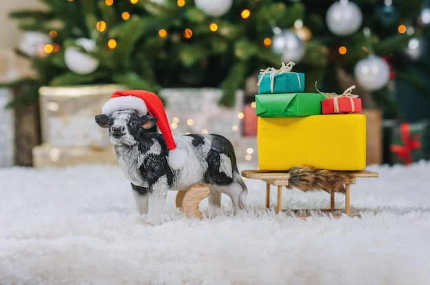 Une vache dans un chapeau de noël porte un traîneau avec des cadeaux sur un fond de noël