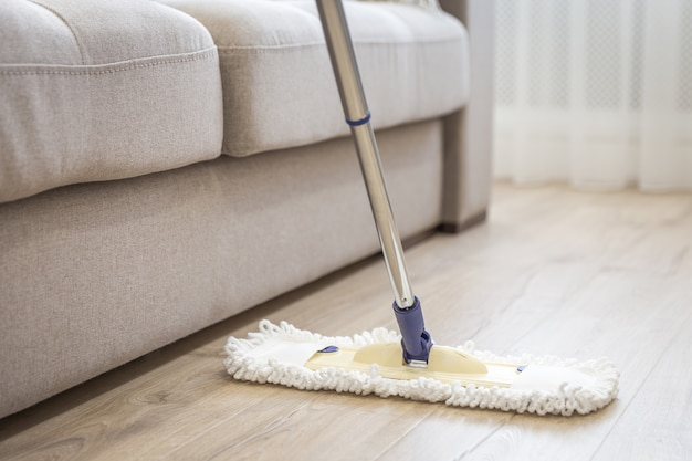 Vadrouille blanche moderne utilisée pour nettoyer un plancher en bois