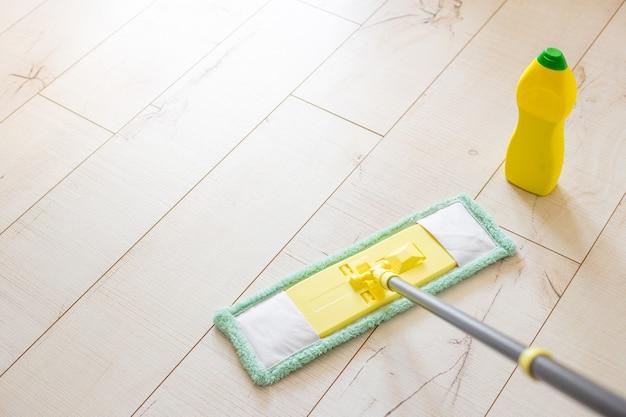 Vadrouille en microfibre jaune isolée sur fond de plancher en bois blanc, gros plan, à l'intérieur. bouteille chimique et bâton de vadrouille