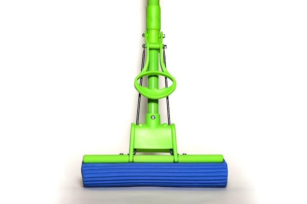 Vadrouille verte avec chiffon en microfibre bleu isolé sur fond blanc en gros plan. vue à la première personne des vadrouilles pour le nettoyage de la maison et le nettoyage des sols. fournitures de maison. concept de nettoyage pour site. espace de copie