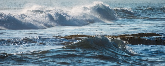 Vague bleue avec bulle frappant sur le littoral en mer tropicale