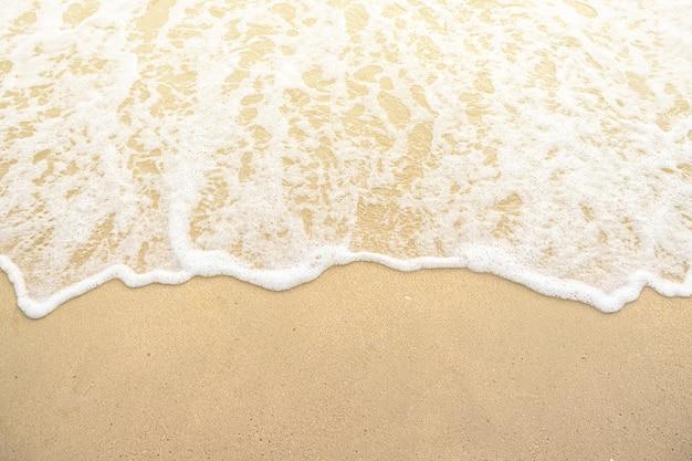 Vague douce sur le coucher de soleil sur la plage de sable