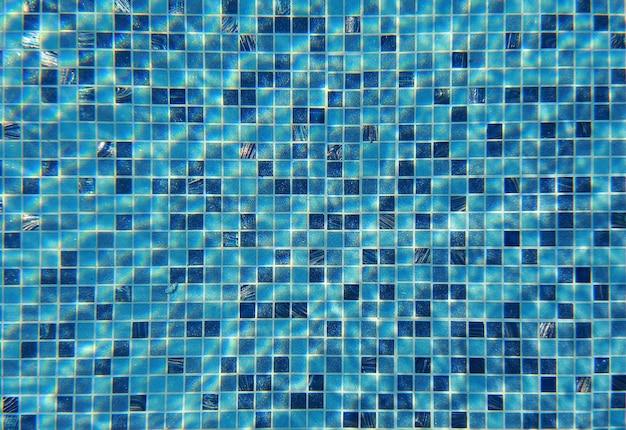 Vague d'eau sous la piscine avec lumière réfléchissante. fond de texture.