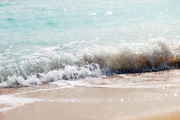 Vague éclaboussant sur une plage.