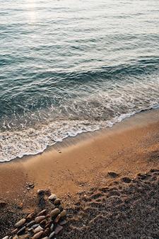 La vague de marée coule sur la plage où se trouvent les pierres
