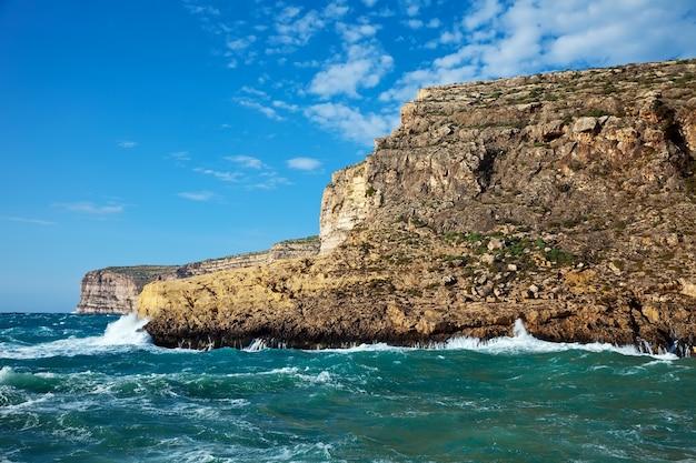 Vague de mer brisée contre la falaise de la côte