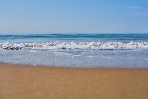 Vague de mer floue avec de la mousse sur une plage de sable