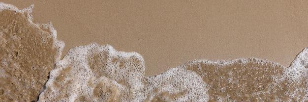 Vague de mer lave la rive sablonneuse du fond de la plage