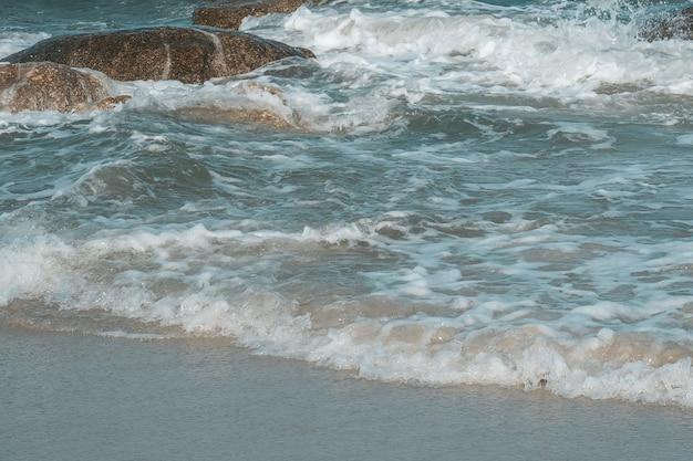 Vague de mer avec de la pierre sur la plage de hua hin, prachuap khiri khan, thaïlande. ton pastel.
