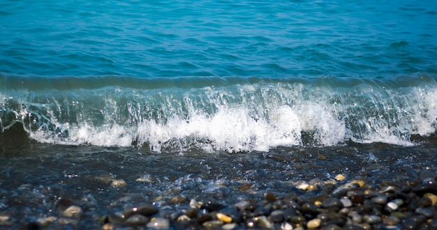 La vague de la mer se brise sur le rivage avec des galets.