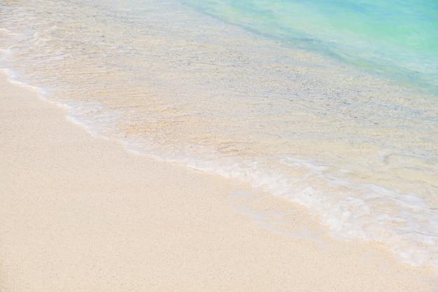 Vague de l'océan bleu sur la plage de sable blanc. fond de texture.