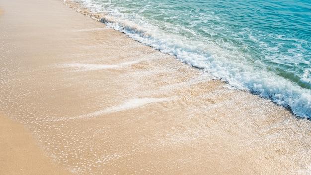 Vague de l'océan bleu sur la plage de sable. fond de texture.