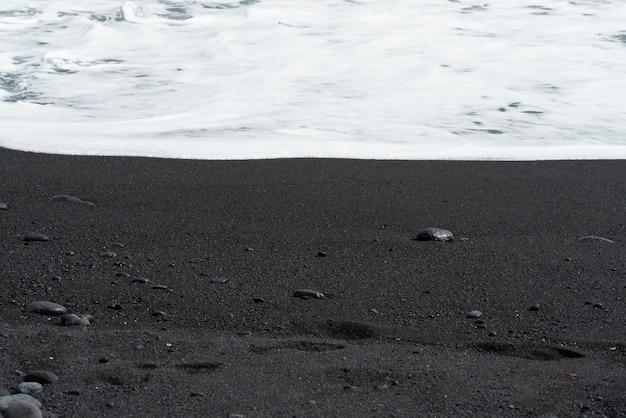 Vague océanique avec de la mousse blanche roule sur une plage de sable noir avec des galets.