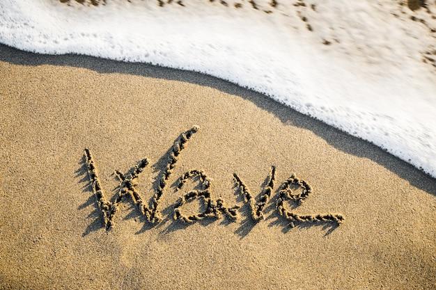 La vague qui vient écrite sur le sable