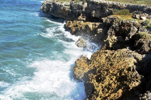 Les vagues bleues frappent les hautes falaises