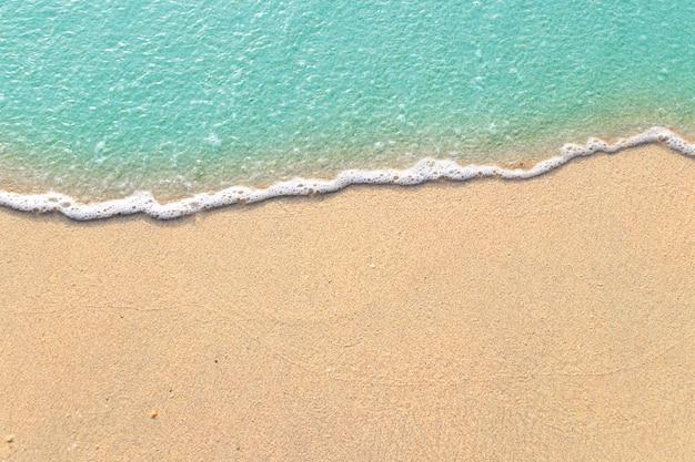 Vagues douces avec de la mousse de l'océan bleu sur la plage de sable