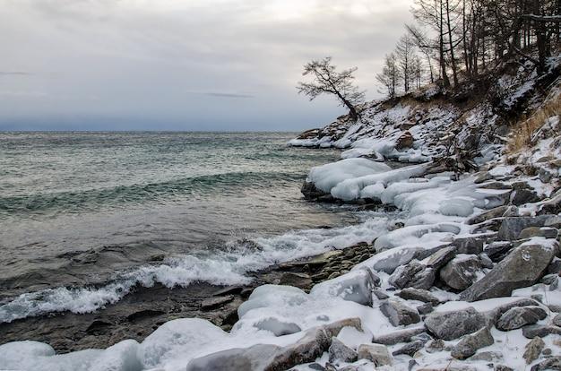Vagues et éclaboussures sur le lac baïkal avec des rochers et des arbres dans la baie d'uzuri