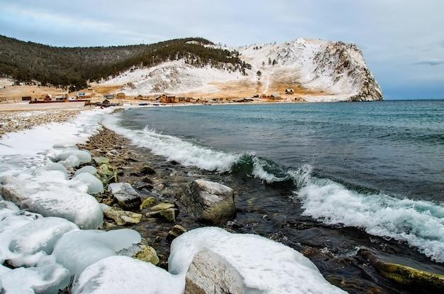 Vagues et éclaboussures sur le lac baïkal avec des rochers et des arbres près du village d'uzuri