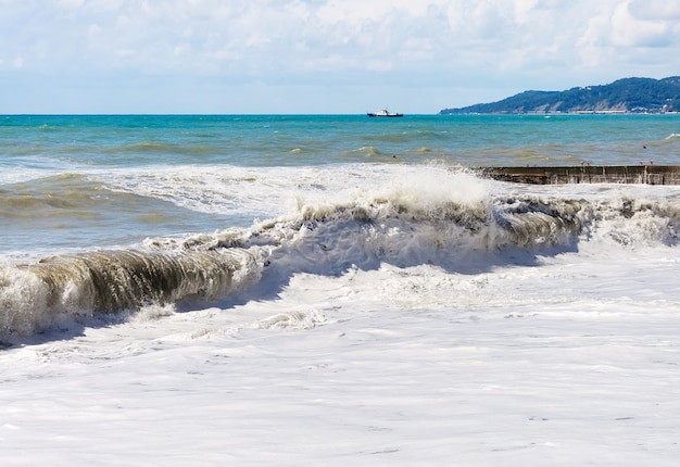 Des vagues d'écume de mer et de tempête ont roulé sur le rivage.