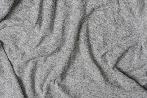Les vagues froissées et froissées de la texture textile des vêtements colorés