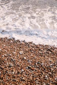 Les vagues de la mer courent sur des cailloux orange sur la plage